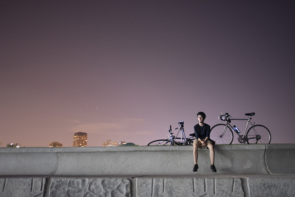 On an incredibly clear summer night in Chicago, my younger brother sits on a ledge next to Lake Michigan. The Big Dipper constellation is barely visible directly above him through the light polluted sky in July 2016.