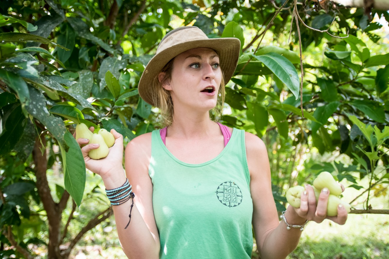 Agriculture Director Zoe St. John holds fruit while leading Medill reporters through the grounds of Kalu Yala.