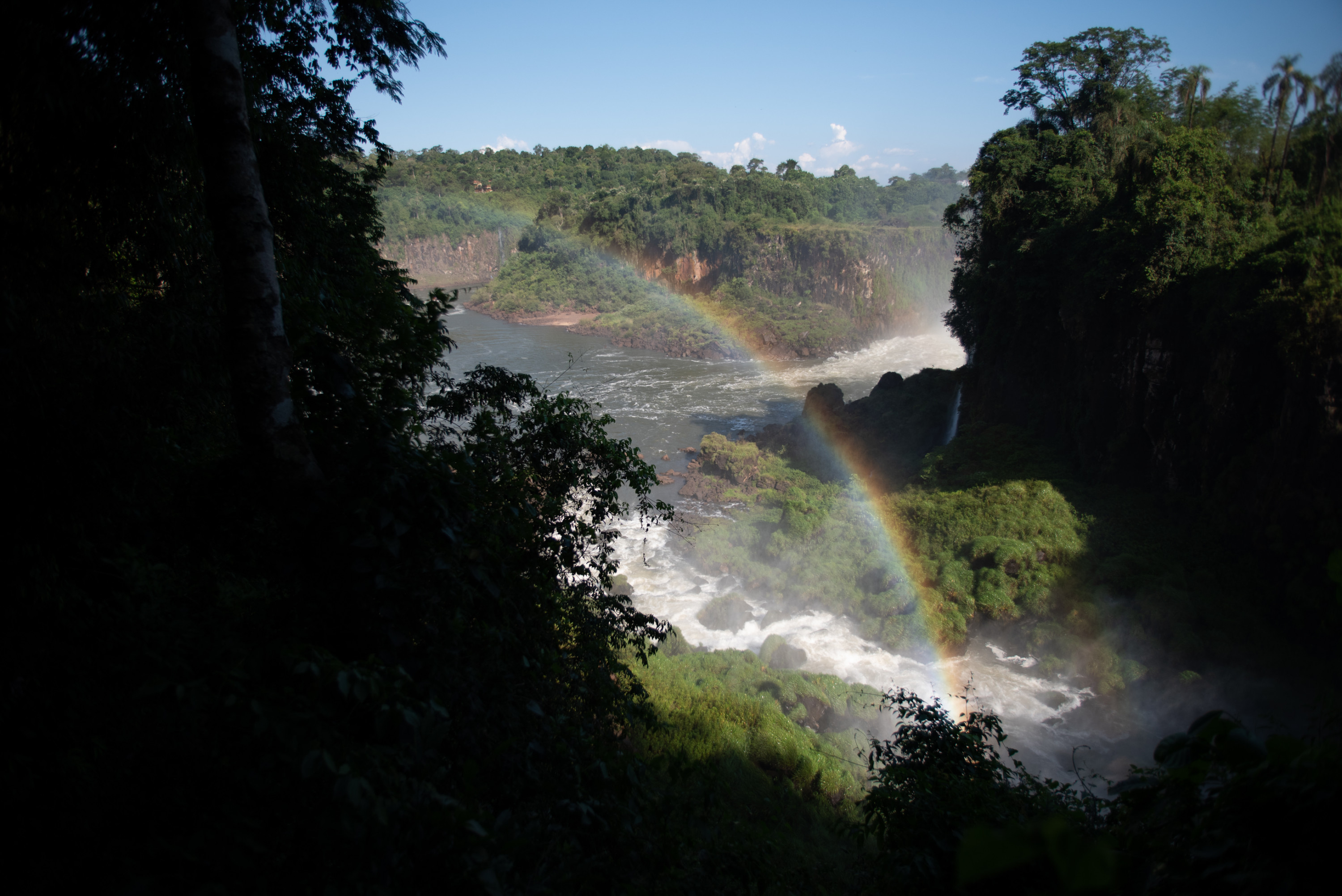 A rainbow stretches across the mist of waterfalls in Iguazú National Park.