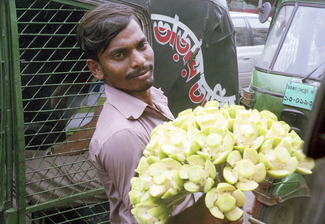 A man sells carved guava to cars trapped in traffic.