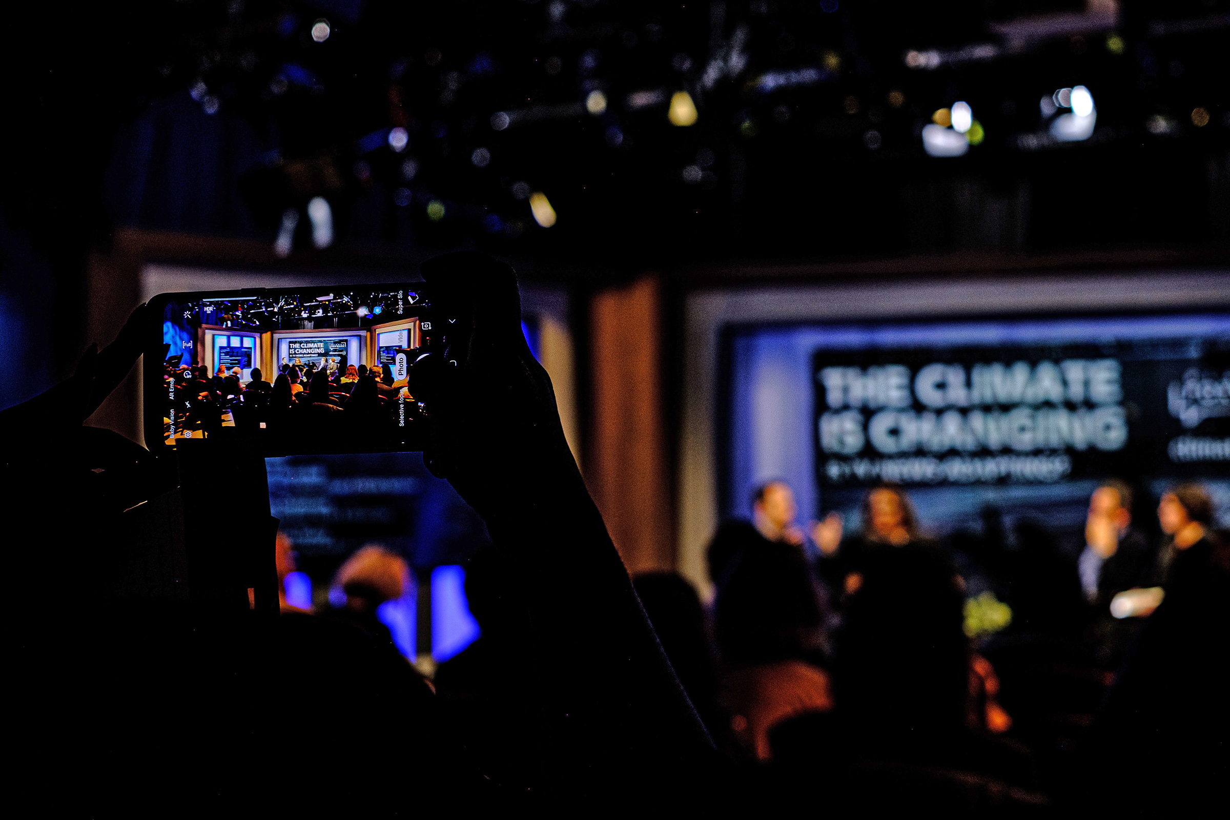 A Climate Nexus staffer snaps a shot of the event from their phone.