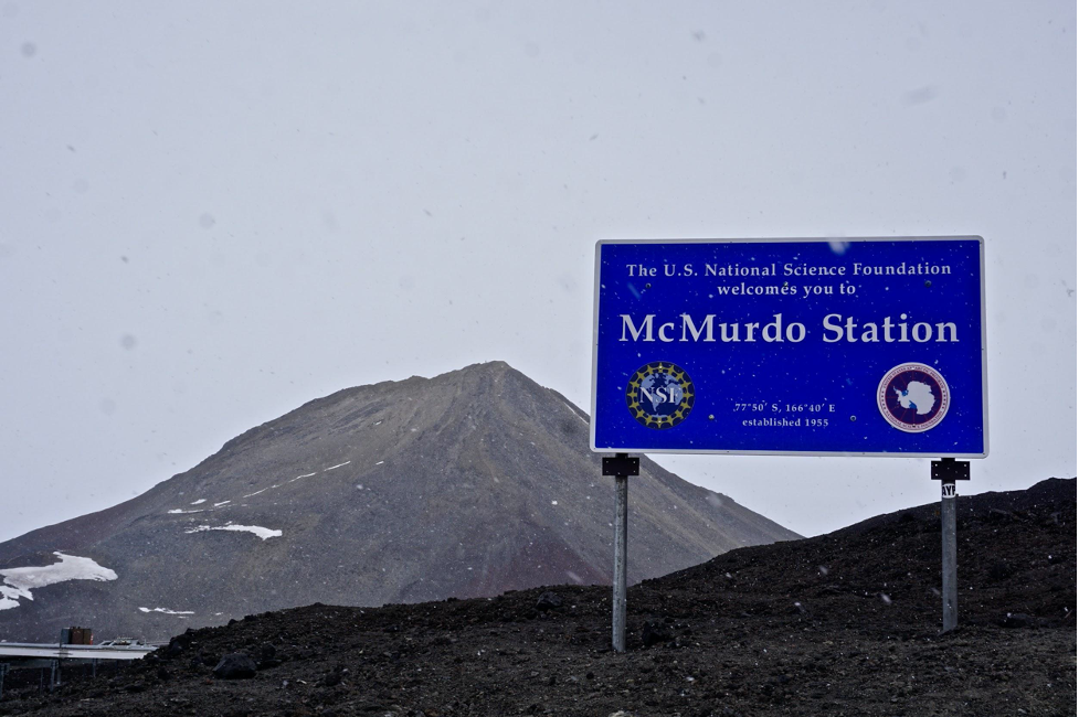 A sign on a rocky hill welcoming visitors to McMurdo Station. McMurdo Station is located on Ross Island, at the southernmost point of solid ground accessible by ship, and is the logistical center of the U.S. Antarctic Program, operated by the National Science Foundation. (Photo courtesy Laura Mattas)