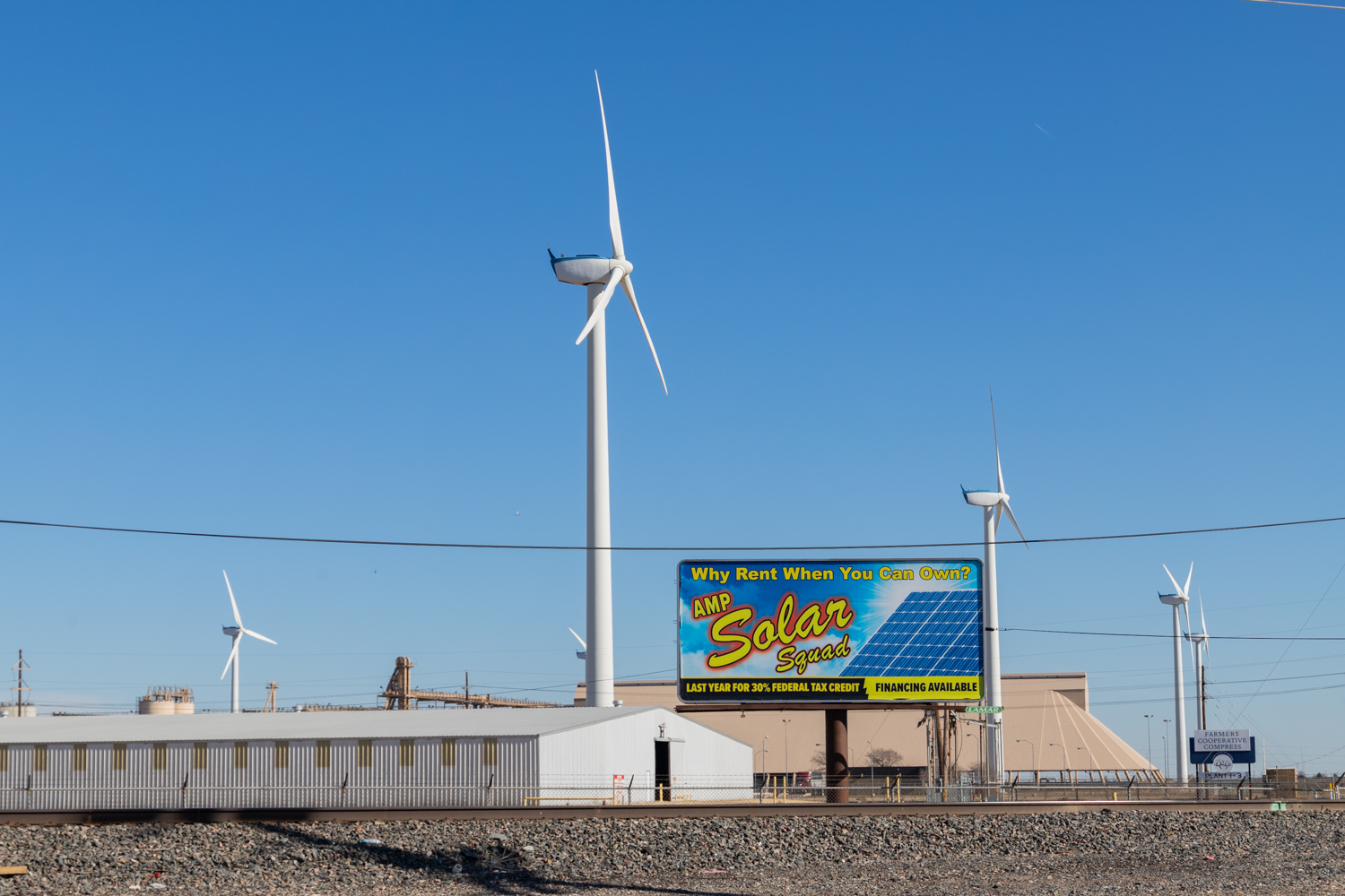 Wind turbines located at the local Cotton Cooperative in Lubbock, Texas spin behind a billboard promoting solar energy. (Codi Clark/Texas Tech University)