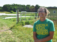 """A young woman in glasses and a shirt that reads """"America needs Lesbian Farmers."""" smiles in front of a background of agricultural fields."""