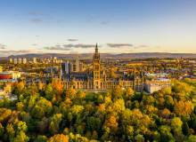 Glasgow university, with a distinctive central spire, is seen from the air, with a cluster of trees turning autumnal colors in the foreground
