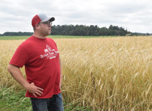 A man in a red t-shirt, blue jeans, a baseball cap, and glasses stands with his hands on this hips looking to the left of the frame, standing in a field of grain.
