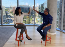 Deepti Bansal Gage, left, and Frank Sesno, right, high five while seated on red stools in front of floor-to-ceiling windows with the DC cityscape in the background