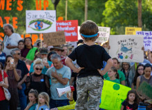 Young boy stands before climate marchers (Jake Meyers/University of Arizona).