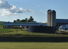A farm, including three tall silos and several buildings, sits on green, grassy land below a blue sky with fluffy, white clouds.