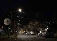 A residential street at night, illuminated by a row of streetlights.