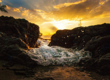 A tide splashing in between two rocks on a coast line as the sun sits low in the sky behind it.