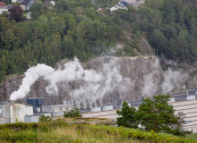 Smoke spreads from a factory to surrounding landscape.