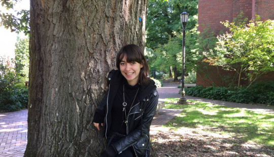 Student activist Giselle Herzfeld poses in front of a tree.