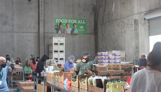 """People in face masks organize food items into cardboard boxes in a gray warehouse space under a green sign that reads """"FOOD FOR ALL."""""""