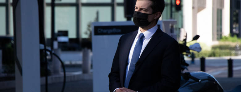 A man in a black suit, blue tie, and black mask stands with his hands interlaced with a EV charging station behind him.