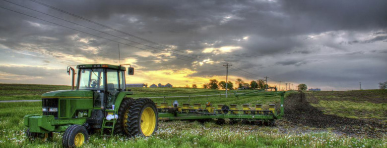 Tractor in a lush field at sunset