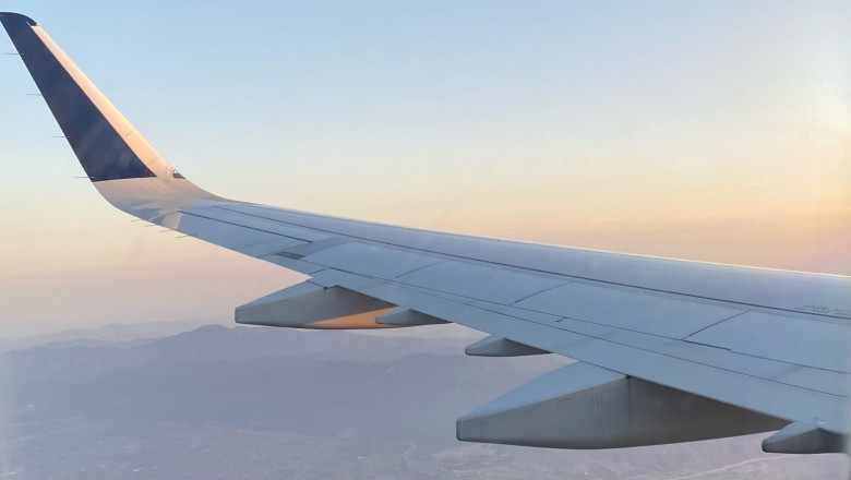 A plane wing in flight from the vantage point of a plane passenger.