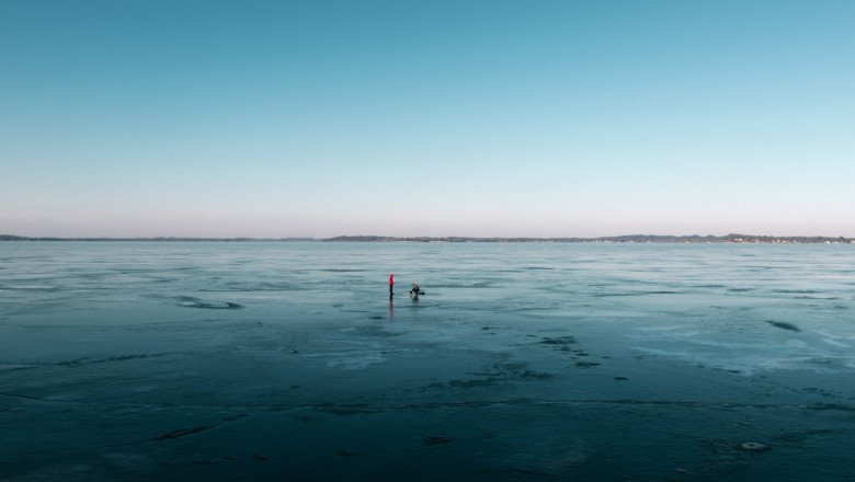 After a week of warmer days the snow melted away from the frozen lake. People were ice fishing on the thinner ice.