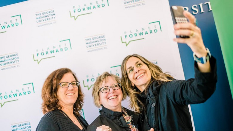 Attendees take a selfie at the Summit in front of the Planet Forward wall.