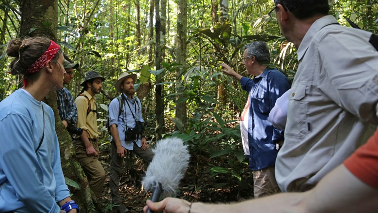 Ze Luis explains about the plant life and the importance of the tree canopy to the group, as Zack Smith records audio for his podcast. (Planet Forward)