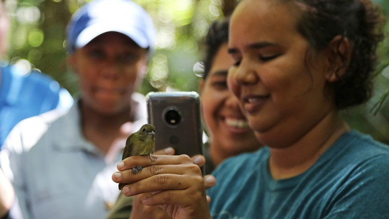 Student researchers document a bird they caught, which unfortunately wasn't the type they were studying. But since it already was banded they recorded that it was caught. (Planet Forward)