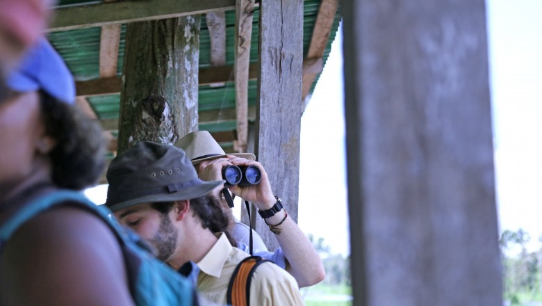 Tomasz Falkowski uses binoculars to get a closer look at the birds in the area. (Planet Forward)
