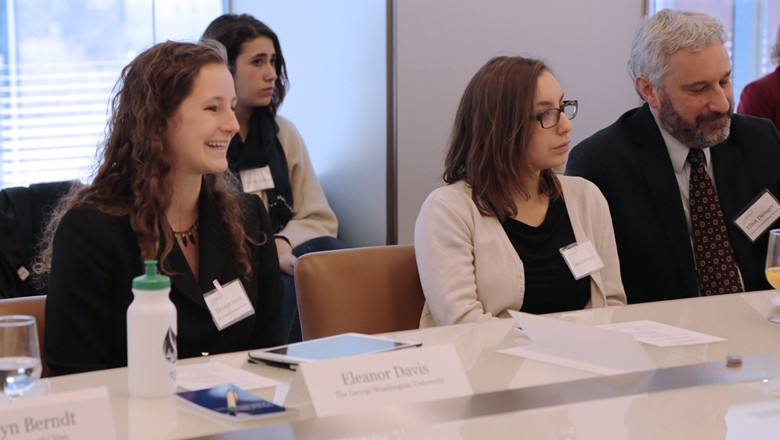 GW senior and COP21 attendee Ellie Davis, left, smiles as she answers a question from the table.