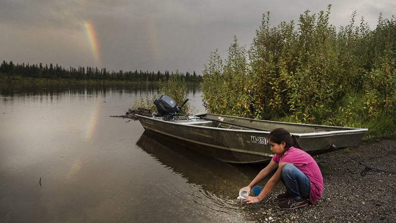 A young girl in the Alaskan village of Shungnak plays in the Kobuk river after a storm. (Jayme Dittmar/University of Montana)