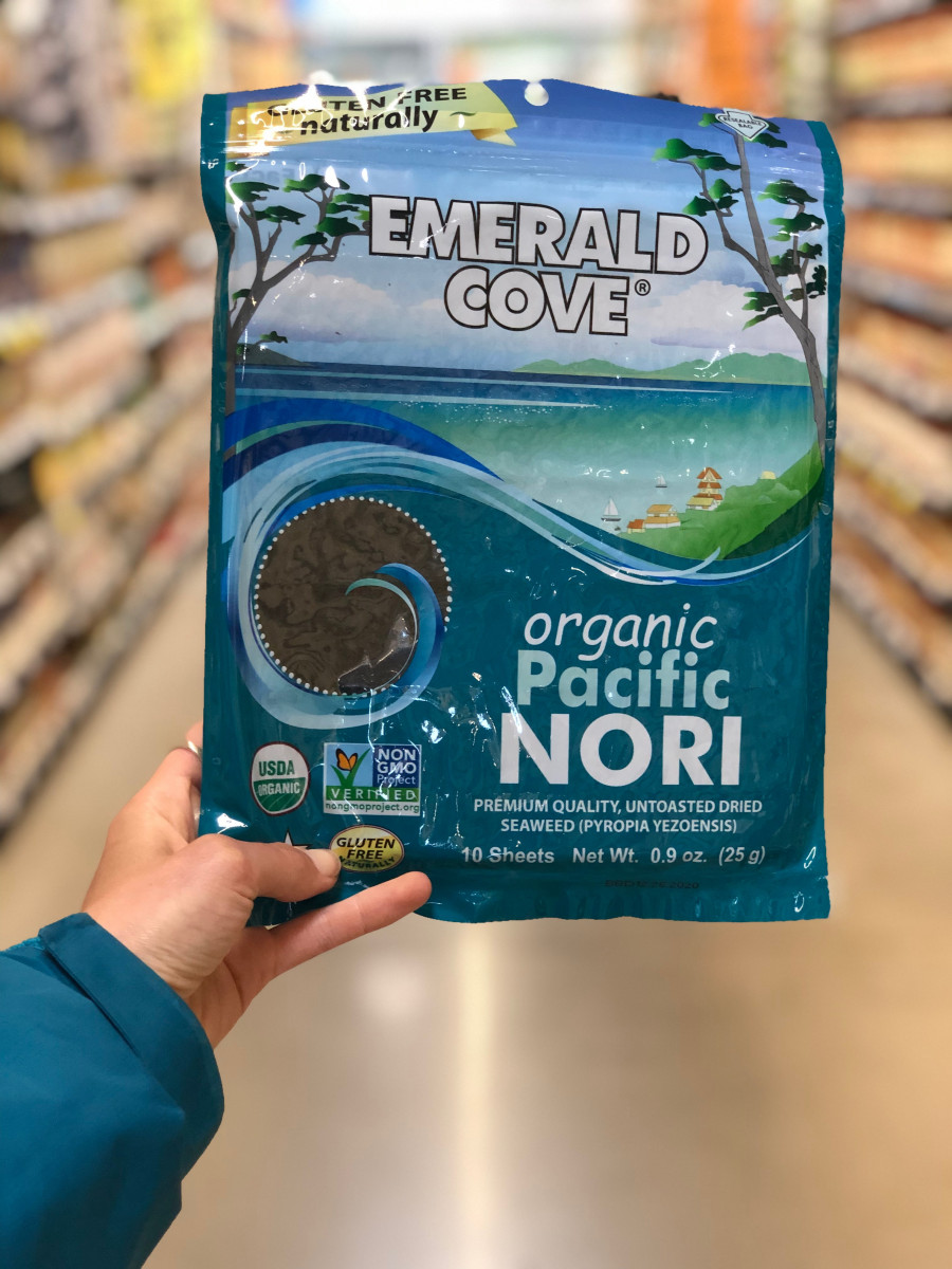 hand holding a package of nori in a supermarket aisle