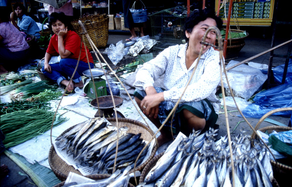 A woman sells fish at a market in Thailand